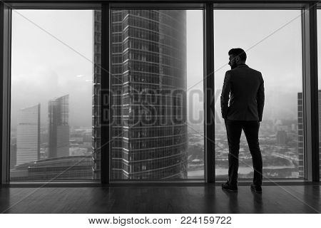 Rearview of a businessman looking out the window at the city.