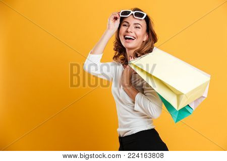 Image of happy young woman standing isolated over yellow background holding shopping bags. Looking camera.