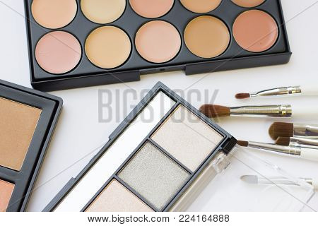 Make Up Beauty Fashion Concept. A set of professional make up products: eyeshadows, eye and lip glitter, face foundation, concealer, contouring, brushes. Decorative cosmetics in black boxes