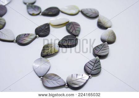 Original necklace with beads in leaves form isolated on white background