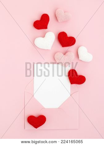 Pink, red and white spreading hearts with valentine greeting card & envelope on pink background. Romantic Love letter. Top view, Minimal style
