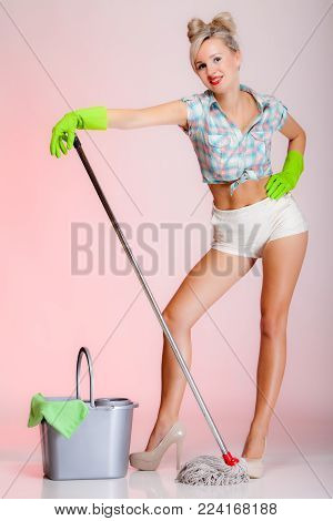 Full length sexy girl retro style with mop, woman housewife cleaner in domestic role. Traditional sharing household chores.  Pin up housework.  Pink background