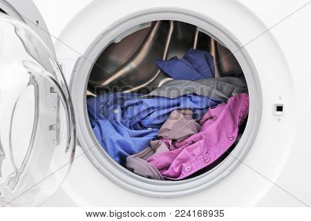 Washing machine with clothes, closeup. Laundry day