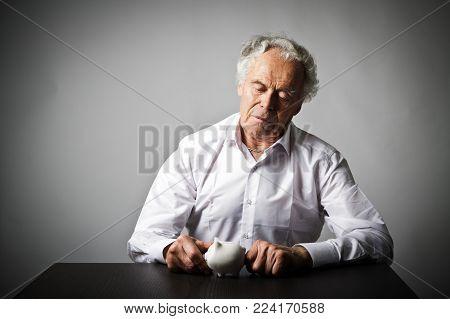 Senior man holding piggy bank. Financial security planning concept.