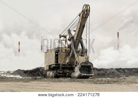 Heavy bucket mining excavator on a crawler track against a background of dense factory strong smog with smoking chimneys. Excavator with mechanical drive and flexible suspension of work equipment.