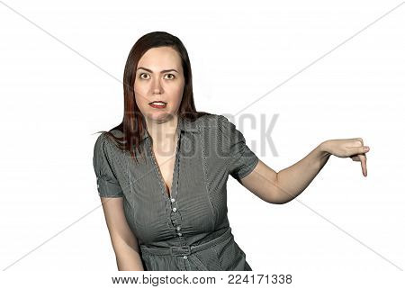 woman on a white background shows a finger at something with an expression of disgust on her face