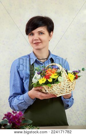 Smiling young female florist working in flower shop. Portrait of beautiful caucasian girl self-employed in flower shop, smiling and looking at camera. A woman florist seller holds a composition of flowers