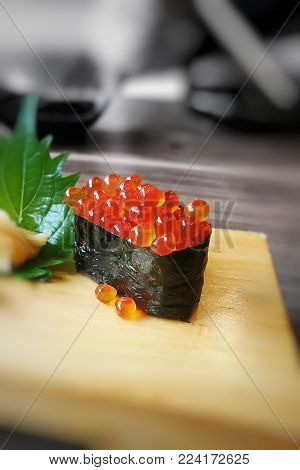 Ikura sushi on wooden plate. Japanese food with ingredients of rice wrapped with nori seaweed, fish eggs (red caviar, salmon roe) on top; blurred b&w background; selective focus; top copy-space.