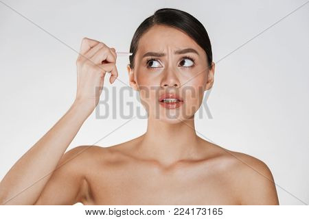 Beauty portrait of sensual brunette woman with hair in bun feeling pain while plucking eyebrows with tweezers isolated over white background