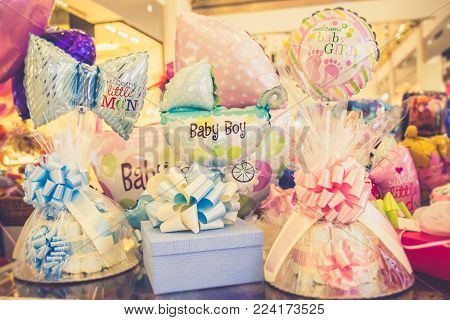Welcome baby girl! Welcome baby boy! Colorful helium balloons and gifts for newborn birthday gift party.