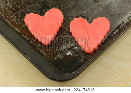 Two red raw heart sugar cookies on weathered baking sheet for Valentine's Day as symbol of love that stays new through  time and hardship