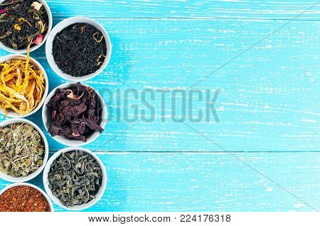Various dried medicinal herbs and teas in several bowls on blue wooden background from above. Copyspace.