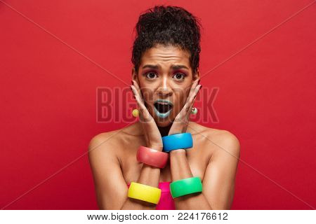 Image of young surprised  woman being bright and stylish grabbing face wearing bracelets on arms over red background