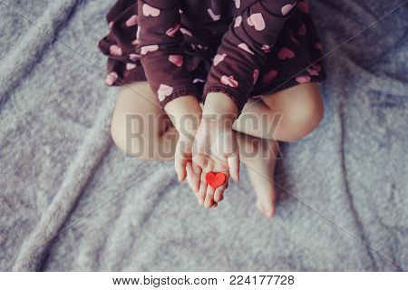 Closeup macro of child with adult parent hands palms holding a bunch of small red and purple paper foam hearts. Lifestyle love and happy childhood concept. Valentines day celebration.