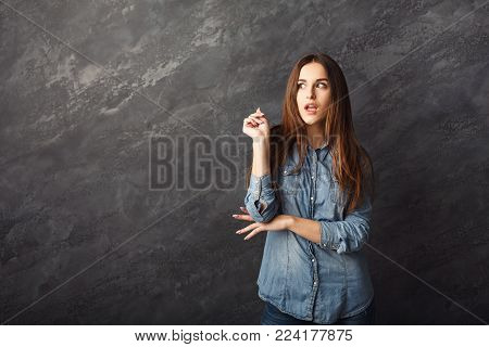 Portrait of thoughtful woman with mysterious look. Pensive girl having cunning idea, dark studio background, copy space