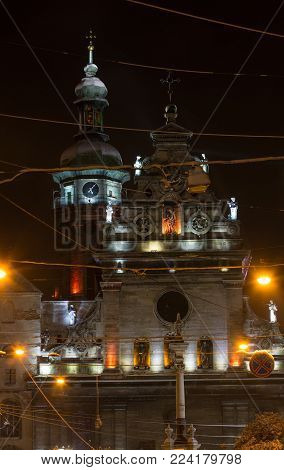 Night winter Lviv city (Ukraine) illuminated cityscape. Bernardine Church and monastery (church of St. Andrew) top, built in17th century. And Monument to Saint John of Dukla ahead, built in 1736.