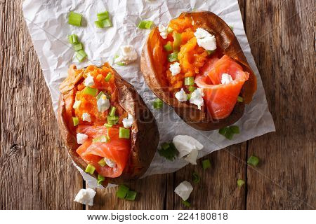 Organic Food: Baked Sweet Potato Stuffed With Red Fish And Green Onion Close-up On Paper. Horizontal