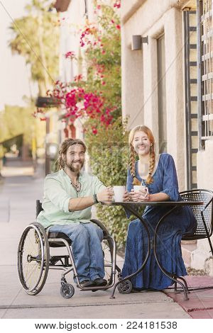 Woman and male friend in wheelchair having coffee