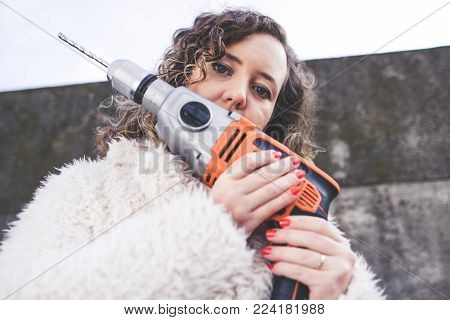 Beautiful curly woman wearing fur coat and drilling in a wall. International Womans Day concept.