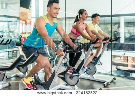 handsome and confident young man smiling while pedaling during group class of HIIT indoor cycling in a modern fitness club