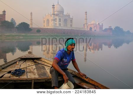 AGRA, INDIA - NOVEMBER 8: Unidentified man bails water out of the boat on Yamuna River near Taj Mahal in the morning on November 8, 2014 in Agra, India. Taj Mahal was designated as a UNESCO World Heritage Site in 1983.