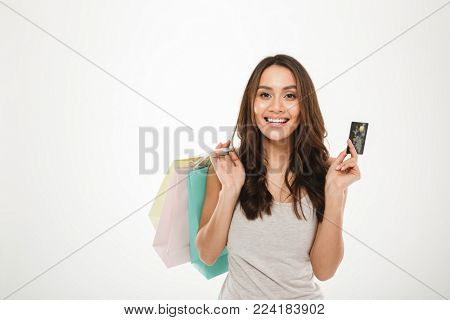 Portrait of rich and trendy woman with buying purchases and paying with credit card isolated over white background