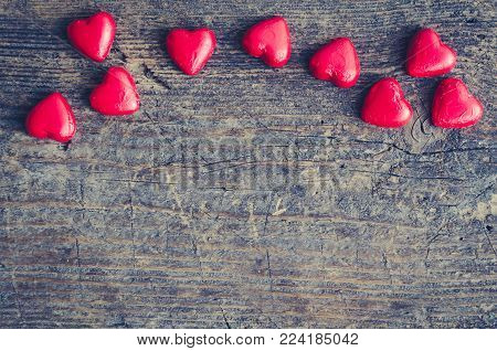 Valentines Day background with red chocolate heart shaped candies on a rustic wooden table with place for text. Romantic love concept. Valentine's greetings card. Copy space. Top view.