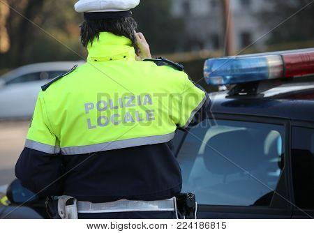 Local Policeman Near The Police Car