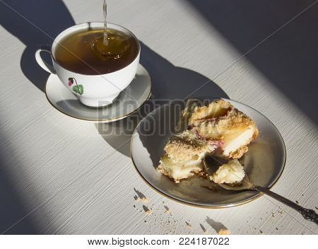 cup of tea and plate with apple pie on white table