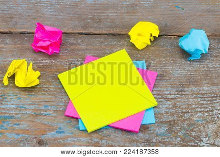 sticky note with crumpled papers  on wooden background, business concept on the sticky note.