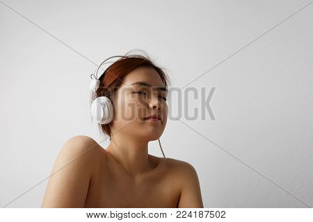 Relaxed woman listening to the music with headphones on white background.