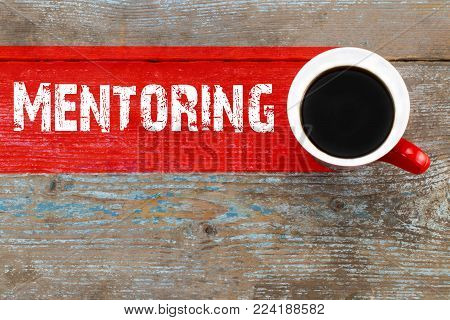Mentoring / Cup of coffee with mentoring inscription on wooden background.
