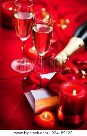 Valentine's Day Romantic Dinner. Date. Table setting with Champagne in two glasses, candles and gift box over holiday red background with hearts. Wedding celebrating
