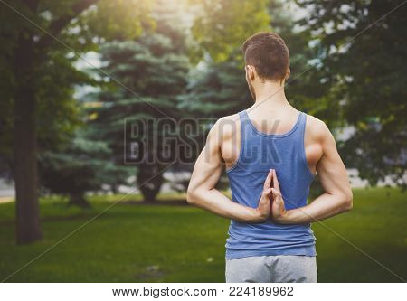 Young man practicing yoga, making asana exercises. Guy do Reverse Prayer Pose, back and shoulders stretching. Healthy lifestyle, copy space