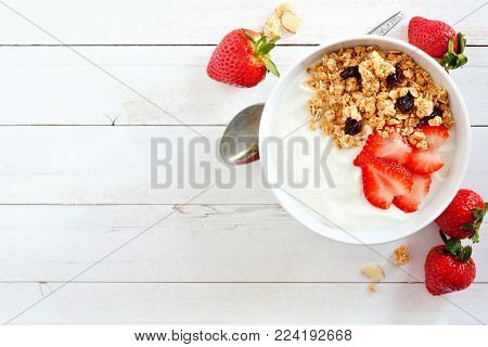 Bowl of yogurt with strawberries and granola, over a white wood background. Flat lay, side orientation.