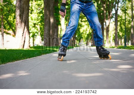 Male legs in blue jeans and roller skates. Man enjoying sports outdoors. Active and healthy lifestyle background, copy space