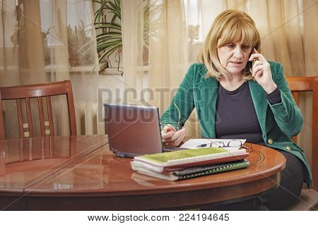 Senior blonde businesswoman having a serious conversation over her cell phone