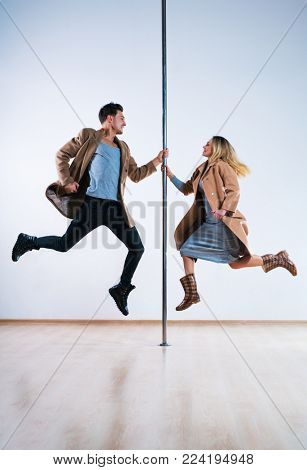 Young man and woman pole dancers in casual autumn clothing jumping
