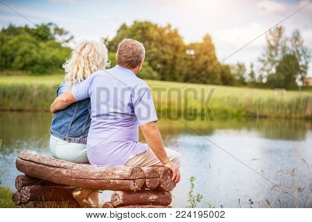 Older marriage sitting together on a bench by the lake. Retirement activities. Happy mature couple.