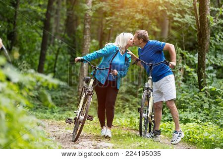 Senior marriage with bicycles kissing fondly in the bosom of nature. Happy couple time.