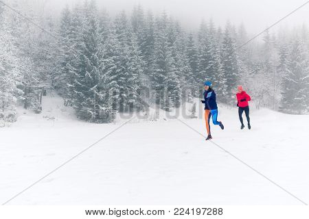 Girls running together on snow in winter mountains. Sport, fitness inspiration and motivation. Two women partners trail running in mountains, winter day. Female trail runner jogging outdoors.