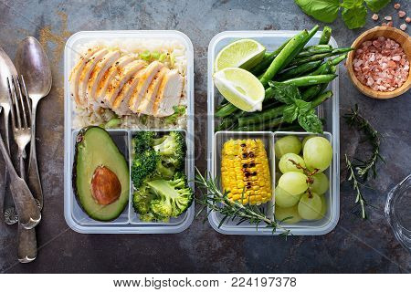 Healthy green meal prep containers with chicken, rice, avocado and vegetables overhead shot