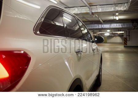 Right side of white modern car at underground parking, side rear view.
