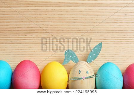 Colorful Easter eggs and one with bunny ears made from paper on wooden background