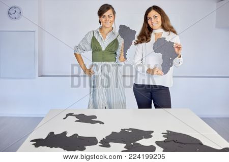 Two smiling woman with fragments of Southern America and Africa in hands stand near table with lots of fragments of map.