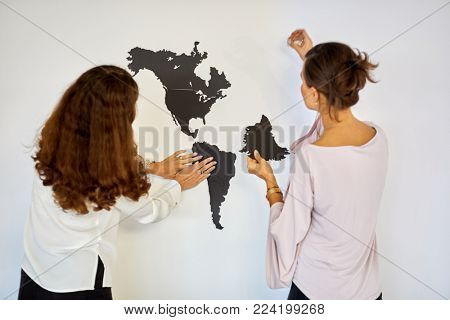 Two women assemble puzzle world map on wall in room.