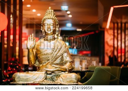 Golden Statue Of Buddha Sitting In Lotus Position With Raised Right Arm Gesture Showing Dispute, Explaining Teachings Of Buddha Vitarka Mudra.