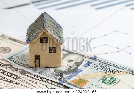 House or real estate buy, sell and investment concept, miniature ceramic house on pile of US dollar banknotes with printed price chart, idea of property invest for future high rising price low risk.