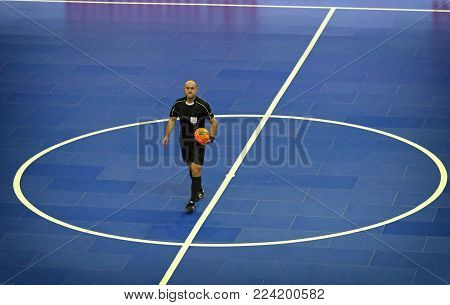 KYIV, UKRAINE - JANUARY 29, 2017: Futsal referee with ball in the center of futsal playground during friendly Futsal match Ukraine v Spain at Palats of Sports in Kyiv, Ukraine