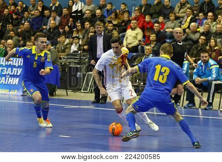 KYIV, UKRAINE - JANUARY 29, 2017: Carlos Ortiz of Spain (in White) attacks during friendly Futsal match against Ukraine at Palats of Sports in Kyiv, Ukraine
